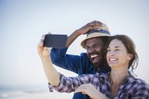 Laughing, enthusiastic multi-ethnic couple taking selfie with camera phone — Stockfoto