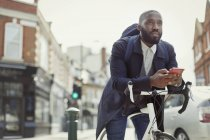 Pensive young businessman texting with cell phone, commuting with bicycle on urban street — Stock Photo