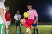 Young female soccer player practicing, bouncing ball on knee on field at night — Stock Photo