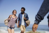 Sorrindo casal multi-étnico de mãos dadas e caminhando na ensolarada praia do oceano de verão — Fotografia de Stock