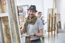Portrait smiling male artist painting at easel in art class studio — Stock Photo