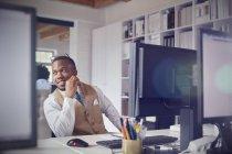 Lächelnder Geschäftsmann am Computer im Büro — Stockfoto