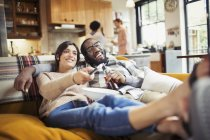 Smiling young couple watching TV, drinking beer and eating popcorn on living room sofa — Stock Photo