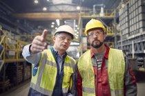 Сталевары разговаривают, жестикулируют на сталелитейном заводе — стоковое фото