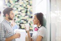 Творчі ділових людей з кавою і навушники говорити в офісі — стокове фото