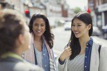 Усміхаючись жінки друзі говорили на міських вулиць — стокове фото