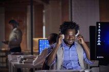 Улыбающийся бизнесмен с наушниками, слушающий музыку, работающий допоздна за компьютером в темном офисе ночью — стоковое фото