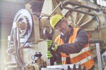 Мужчина работает с помощью большого гаечного ключа на заводе — стоковое фото