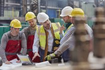 Male foreman, engineers and workers at laptop meeting, discussing blueprints in factory — Stock Photo