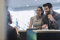 Sonriente pareja de clientes hablando con la recepcionista en el escritorio en la concesionaria de automóviles — Stock Photo