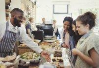 Мужского пола работника, помогая клиентов женщин в кафе — стоковое фото