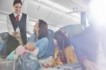 Smiling flight attendant bringing baby bottle to mother with baby on airplane — Stock Photo