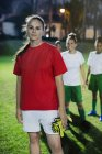 Portrait confident young female soccer player on field at night — Stock Photo