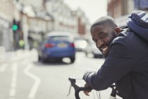 Smiling young businessman commuting, riding bicycle on sunny urban street — Stock Photo