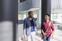 Empresários conversando e caminhando no lobby de escritório moderno — Fotografia de Stock