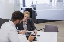 Smiling car saleswoman showing brochure to male customer in car dealership office — Stock Photo