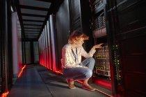 Female IT technician examining panel in dark server room — Stock Photo