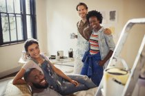 Portrait smiling couples painting living room — Stock Photo