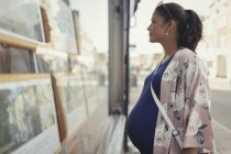 Pregnant woman browsing real estate listings at urban storefront — Stock Photo