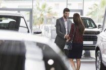 Приветствие продавца автомобилей, рукопожатие с клиенткой в салоне автосалона — стоковое фото