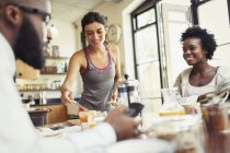 Friend roommates eating breakfast in kitchen — Stock Photo