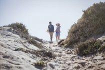 Coppie che camminano sul percorso della spiaggia estate pieno di sole — Foto stock