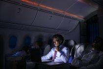 Businessman working at laptop on night airplane — Stock Photo