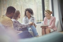 Smiling woman comforting woman in group therapy session — Stock Photo