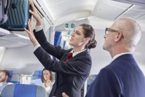 Flight attendant helping businessman place luggage in overhead compartment on airplane — Stockfoto