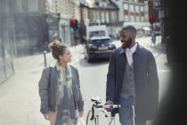 Couple walking, commuting with bicycle on urban street — Stock Photo