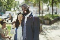 Портрет, посміхаючись, ласкава молода пара обіймає в Сонячний парк — стокове фото