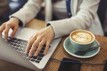 Manos de mujer joven usando el ordenador portátil, beber capuchino en la cafetería - foto de stock