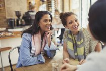 Smiling women friends talking at cafe table — Stock Photo