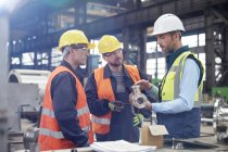 Male engineers discussing steel part in factory — Stock Photo
