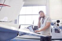 Mécanicien avion Male parler sur téléphone portable et travailler à l'ordinateur portable dans le hangar — Photo de stock