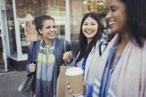 Улыбающиеся подруги с пакетами для покупок и кофе у входа в магазин — стоковое фото