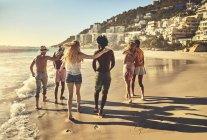 Giovani amici di coppia a piedi sulla spiaggia estiva soleggiata — Foto stock