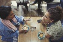 Молоді жінки друзі говорити і пити капучіно в кафе таблиці — стокове фото