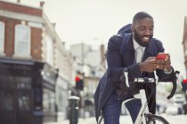 Young businessman commuting with bicycle, texting with cell phone on sunny urban street — Stock Photo
