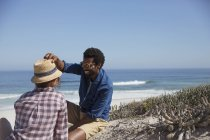 Smiling man placing hat on girlfriend on sunny summer ocean beach — Stock Photo