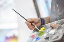 Acercamiento artista sumergiendo pincel en pintura amarilla en la paleta - foto de stock