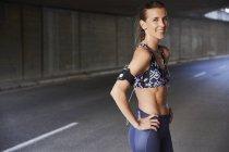 Ritratto sorridente in forma femminile del corridore nel reggiseno di sport con fascia da braccio lettore mp3 e cuffie nel tunnel urbano — Foto stock