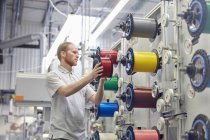 Мужчина меняет катушки на станках на заводе волоконной оптики — стоковое фото