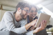 Smiling couple with headphones using digital tablet — Stock Photo