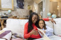 Mother and daughter looking at photo album on sofa — Stock Photo