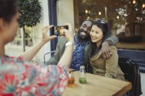 Woman photographing affectionate couple friends with camera phone at sidewalk cafe — Stock Photo