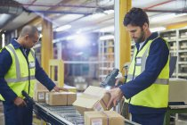 Workers scanning and processing boxes on conveyor belt in distribution warehouse — Stock Photo