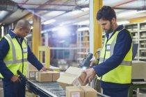 Arbeiter scannen und verarbeiten Boxen auf Förderbändern im Auslieferungslager — Stockfoto