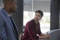 Uomini d'affari che parlano sul balcone dell'ufficio moderno — Foto stock