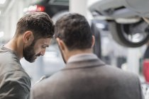 Male mechanic and customer talking, looking down in auto repair shop — Stock Photo